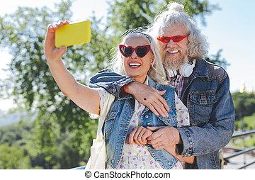 Nice cheerful woman holding her smartphone