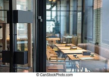Modern door handle on the wooden glass door in front of the cafe.