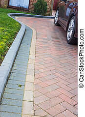 A modern driveway, with different coloured paving, forming patterns and a curved shape.