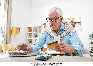 Modern elderly man buying online