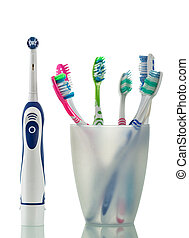 Modern electric and manual toothbrushes stand in glass...