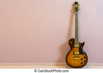 modern electric guitar with tree of life neck inlay, isolated on stone wall background