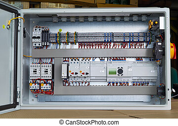 Modern electrical control Cabinet with controller and circuit breakers.