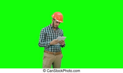 Modern engineer using a wireless tablet to check construction project on a Green Screen, Chroma Key.