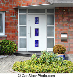 Modern entry door with a front garden of the house -...