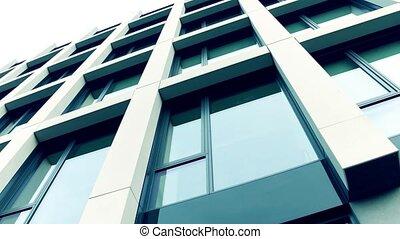 Modern expensive business district. Office building big windows, low angle 4K steadicam shot