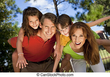 A modern family of father, mother, daughter and son playing together and having doing piggy back in a park