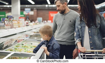 Modern family is buying precooked frozen food in supermarket, boy is opening refrigerator and taking bag, his parents are checking expiry date and ingredients contents.