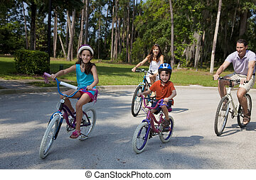 A modern family of two parents and two children, a boy and a girl, cycling together.