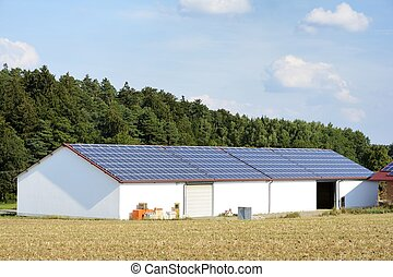 Modern farm - Barn of a farm with solar panels on the roof