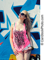 Modern fashion sexy girl in sunglasses posing near a blue wall graffiti