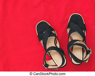 Modern fashionable summer women's shoes on red fabric. Flat lay.