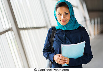modern female middle eastern college student holding a book