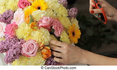 Modern florist puts pale yellow carnations in a bouquet of tulips, lilacs, roses and other colorful flowers
