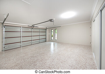 The inside of a modern 2 bay home garage with pebble floor and dual auto garage door