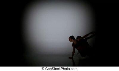 Modern girl dancing acrobatic contemporary on black background, spot light