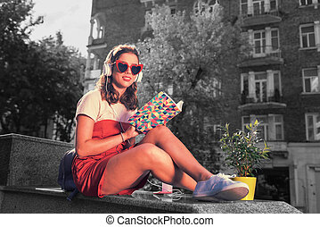 Modern girl reading her book while sitting outside waiting for best friend
