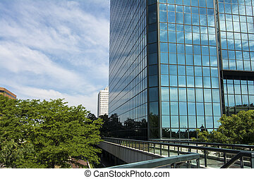 A partial view of downtown Toledo Ohio skyscraper. Made with large glass windows that reflect the beautiful blue sky and white clouds.