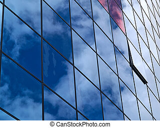Modern glass building with reflection of clouds