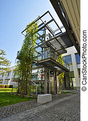 modern glass elevator shaft on the street, overgrown with...
