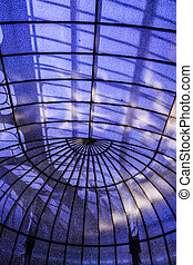Modern glass roof with blue sky and sun