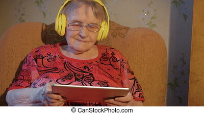 Senior woman is sitting in armchair with tablet PC in hands and wireless headphones on head.