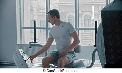 Modern gym - a man sitting down on the training apparatus and training his hands. Mid shot