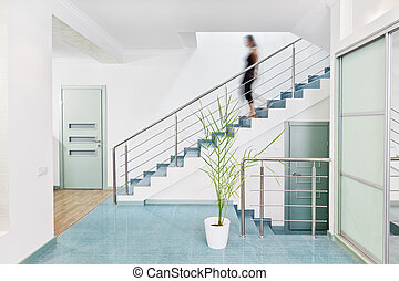 Modern hall interior in minimalism style with blurred person moving downstairs