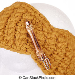Modern handmade woollen knitted headband on a white Doll head