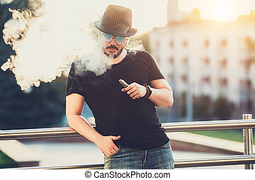 Modern happy young man in hat with a beard fun Vaporizers,...