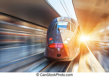 Modern high speed train on a clear day with motion blur at the city station.
