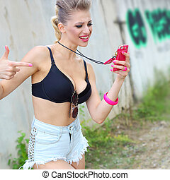 Modern hipster girl emotionally speaks on the phone. Crazy fashionable girl swearing on the phone.