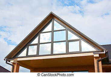 Modern house attic construction with roof guttering and panoramic mansard, attic skylight window.  Attic skylight glass wall.