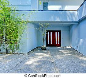 Modern house exterior. Entrance with burgundy door