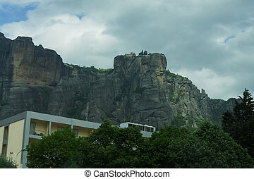 Modern house on Meteora cloudy mountains background.