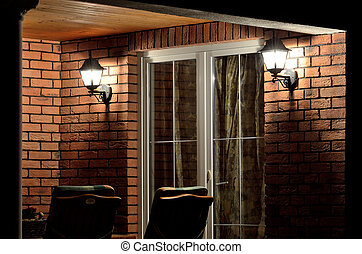 Modern house terrace (patio) with garden furniture at night