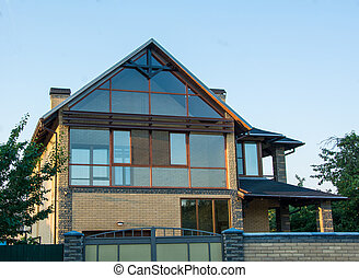 Modern house with glazed facade. Brick house with panoramic windows