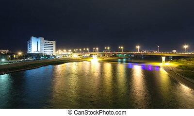 Modern houses and illuminated bridge on the riverside Ural...