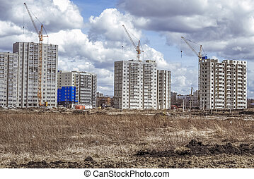 Modern houses under construction and construction cranes