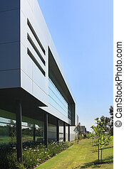 A modern industrial building, with surrounding garden beds, and clear blue sky.