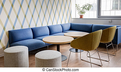 modern interior with blue sofas and round tables in the business center