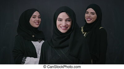 Group portrait of beautiful Muslim women in a fashionable dress with hijab isolated on black chalkboard background