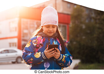 Modern kid girl use smartphone in outdoor with sunlight