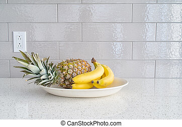 Modern kitchen countertop with fruits dish against gray backsplash