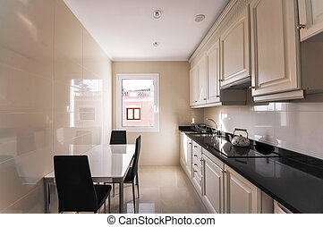 Modern kitchen interior. Design of a narrow kitchen with a small table and three chairs. Comfortable hob and modern furniture. Marble floors, tiles on the walls