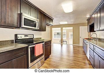 Modern kitchen room interior with deep brown cabinets