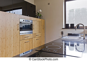 Modern kitchen with electric cooktop and wooden units in a...