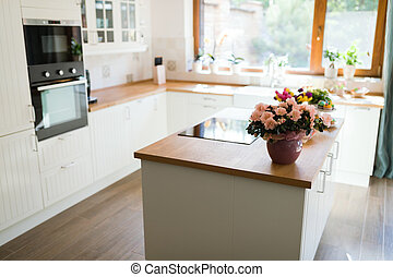 Modern kitchen with flowers on the worktop