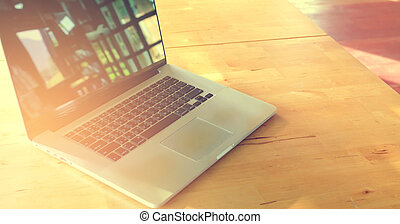 modern laptop on wood table with sunlight