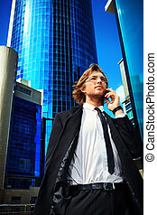 Young businessman talking on his mobile phone in the big city.